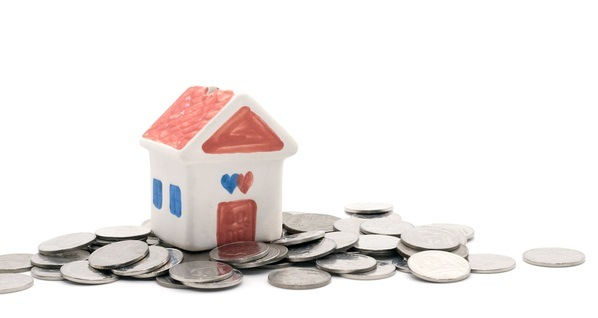 House on a pile of coins on white background